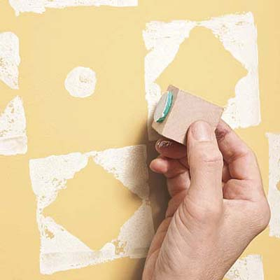 using the circle stamp on a yellow-painted wall
