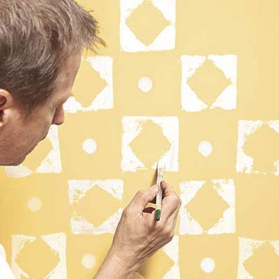man using paint brush to fill in the thin spots after using a stamp to create a decorative pattern