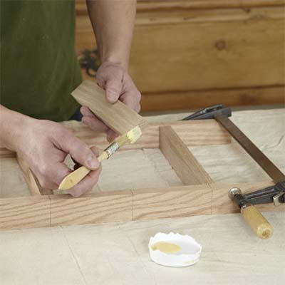 hands brushing glue onto the spindles for building a dog gate