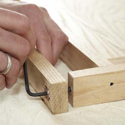 hands using an allen wrench to attach the feet while building a dog gate