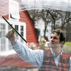 man wiping away a soapy window pane with a squeegee