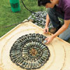 Mark Powers making a test version of his pebble mosaic in a miniature sandbox
