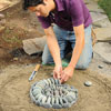 Mark Powers filling in the spiral pattern in his pebble mosaic