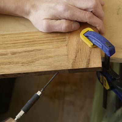 Mark Powers uses a drill/driver to put a pilot hole into the door frame of a dog crate