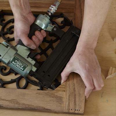 Mark Powers uses a pneumatic brad nailer to attach corner blocks to the door frame of a dog crate