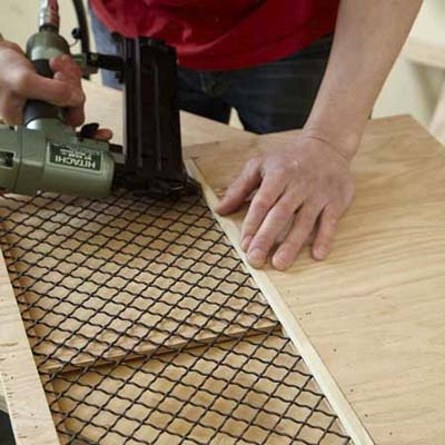 Mark Powers attaches the grille to the side windows for a side panel of a dog crate