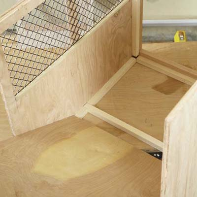 Mark Powers inserts the floorboard into the bottom of a dog crate