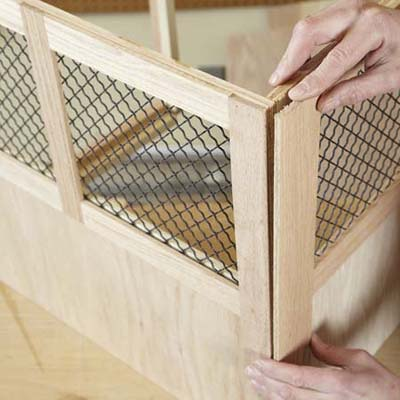 Mark Powers attaches a stile to a back panel of a dog crate