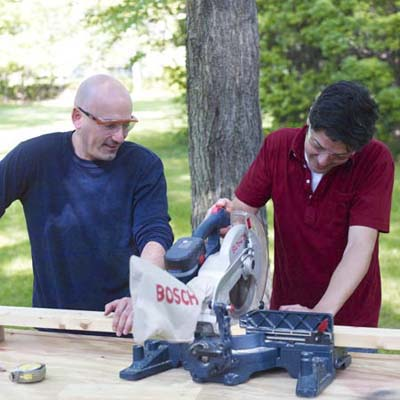 two men sawing a two by four for ladder golf game set