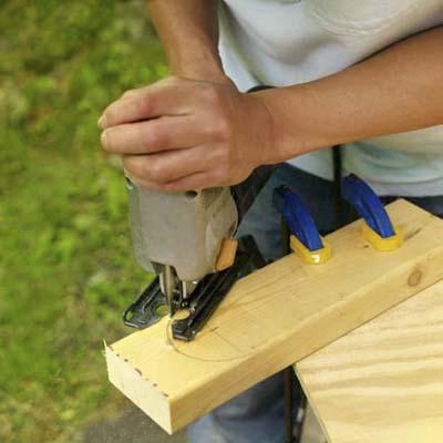 man making legs for cornhole game board