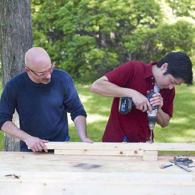 two men drilling holes in rungs for ladder golf game set