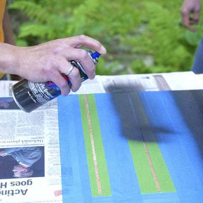 people taping off and painting the lines while building a ricochet game board