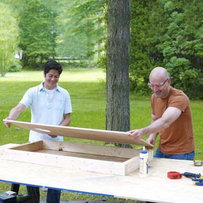 two men positioning frames for cornhole game board