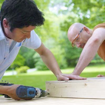 two men assembling frames for cornhole game board
