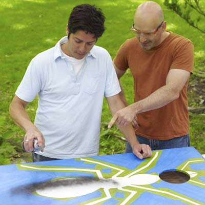 two men painting design for cornhole game board