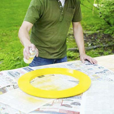 man spray painting wood ring for shishkaball game