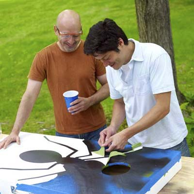 two men removing tape of design for cornhole game board