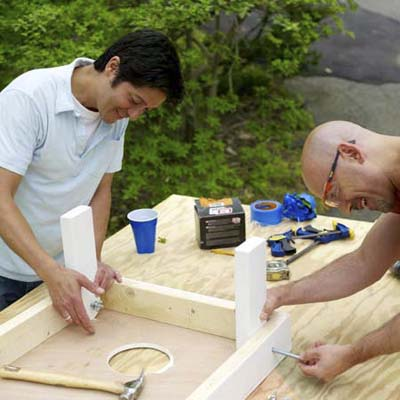 two men attaching legs for cornhole game board