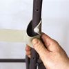 man securing vinyl strap onto outdoor patio chair frame