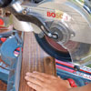 Mark Powers cuts the decking boards for the bench seats with a compound miter saw