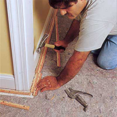 person installing tack strip to demonstrate how install carpet