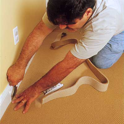 two people using a wide-blade carpet chisel to demonstrate how-to install carpet