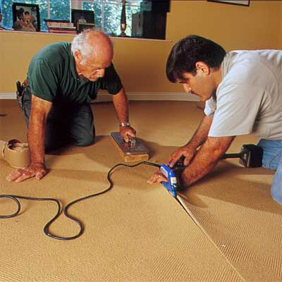 two people using an electric seaming iron to demonstrate how-to install carpet