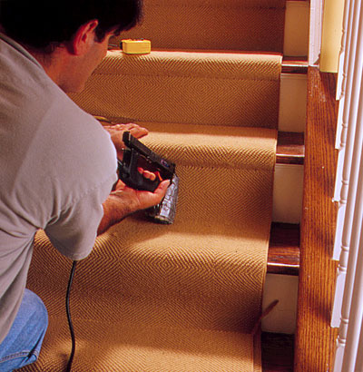 person tacking carpet to a tread to demonstrate how-to install carpet