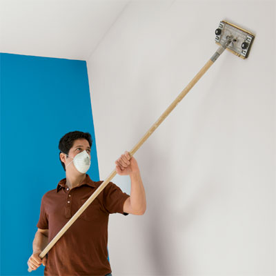 man sanding a wall using a sanding pole and sandpaper