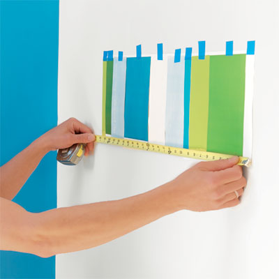 hands measuring a completed pattern to repeat when painting a striped wall
