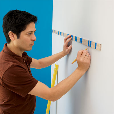 person using a story stick to mark the wall where stripes will be painted