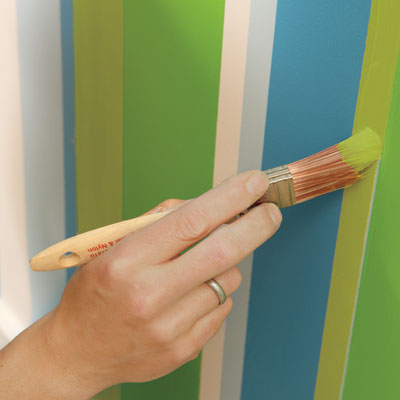 touch up the stripes to finish painting a striped wall