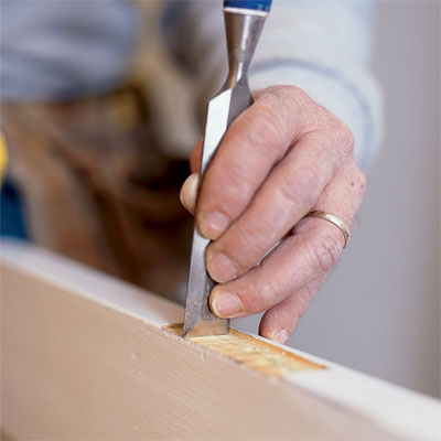hand using a chisel to fix a stuck door