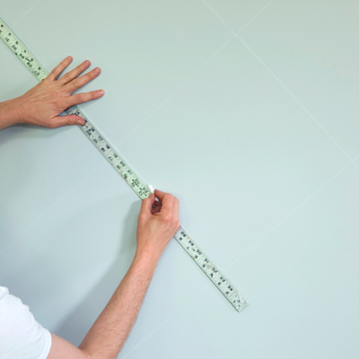 man using yardstick to make chalk grid for wall stenciling