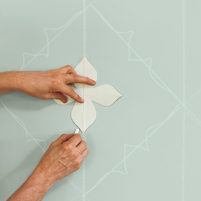 man using paper template to create painted wall design