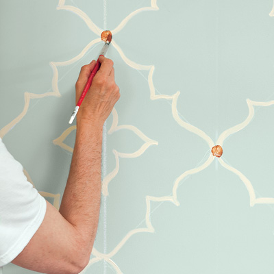 man painting moroccan wall design