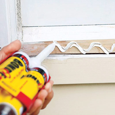 man applying adhesive for installing new windowsill
