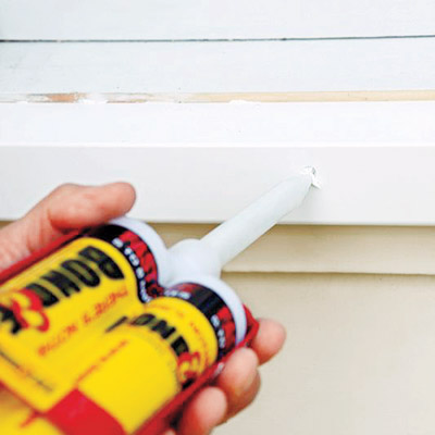 man covering screwheads on new windowsill with white adhesive