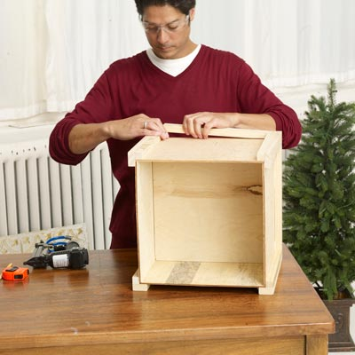 Mark Powers adds trim to the bottom of the x-mas tree box stand