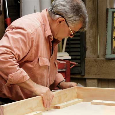 Tom Silva attaches an apron to the table top for a trestle table