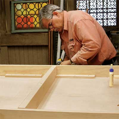 Tom Silva attaches stringers to the table top for a trestle table