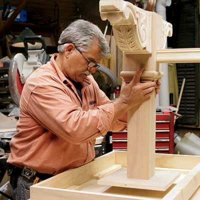 Tom Silva positions the leg assembly to the underside of the table top for a trestle table