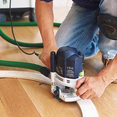 using a router to make a circular cut in the floor to accommodate a floor medallion