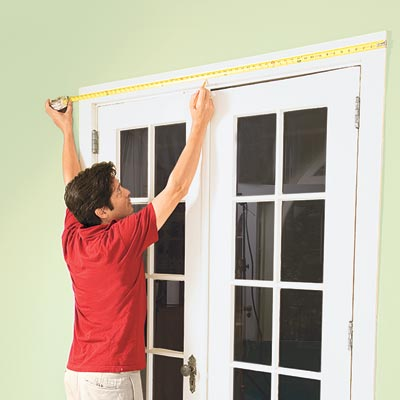 Mark Powers measures the top casing above a set of French doors