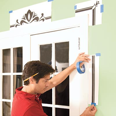 Mark Powers tapes a printout of the stencil pattern around the French doors for reference