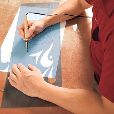 Mark Powers cuts the curved lines of the stencil pattern with an electric stencil-cutting pen