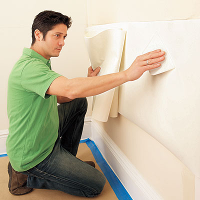 using a smoother to affix the liner to the wall before applying the wainscot