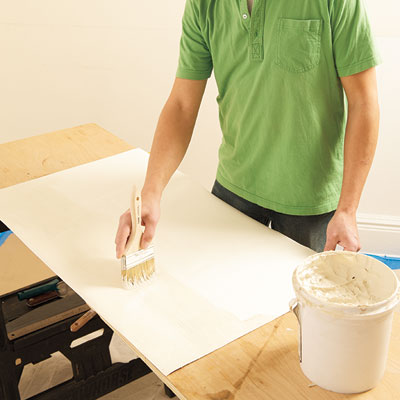 applying adhesive to the back of a Lincrusta wainscot panel with a brush