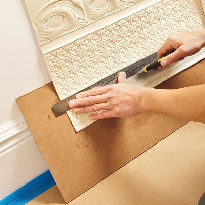 placing a board behind the bottom of the Lincrusta wainscot panel and trimming away excess with a straightedge and a utility knife