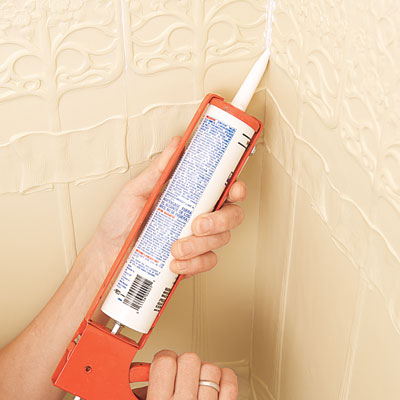 applying caulk to the corner of the installed Lincrusta wainscot panels